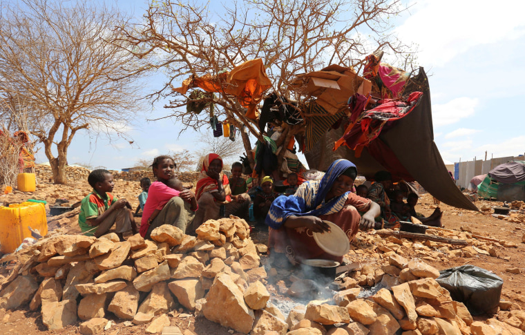 Image: An internally displaced Somali woman prepares a meal outside her shelter after fleeing from drought stricken regions in Baidoa, March 26.