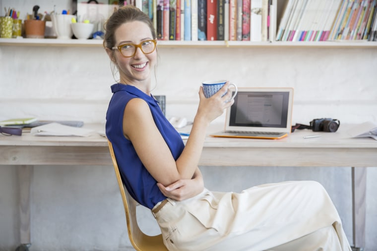 Image: Young woman sits with mug in home office