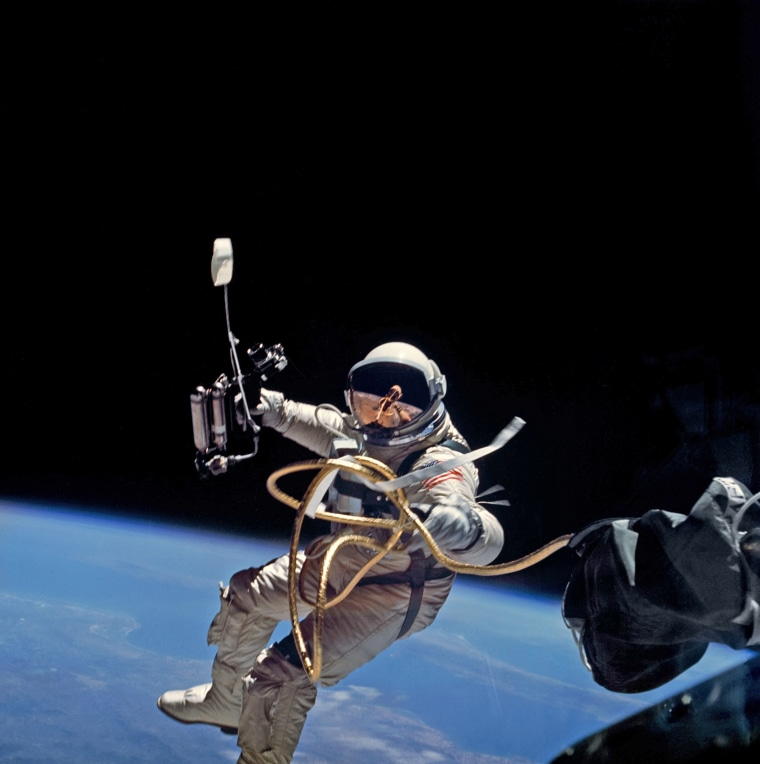 S65-34635 (3 June 1965) --- Astronaut Edward H. White II, pilot on the Gemini-Titan 4 spaceflight, is shown during his egress from the spacecraft. His face is covered by a shaded visor to protect him from the unfiltered rays of the sun. White became the first American astronaut to walk in space. He remained outside the spacecraft for 21 minutes during the third revolution of the Gemini-4 mission. He wears a specially designed spacesuit for the extravehicular activity (EVA). In his right hand, he carries a Hand-Held Self-Maneuvering Unit (HHSMU) with which he controlled his movements while in space. He was attached to the spacecraft by a 25-feet umbilical line and a 23-feet tether line,