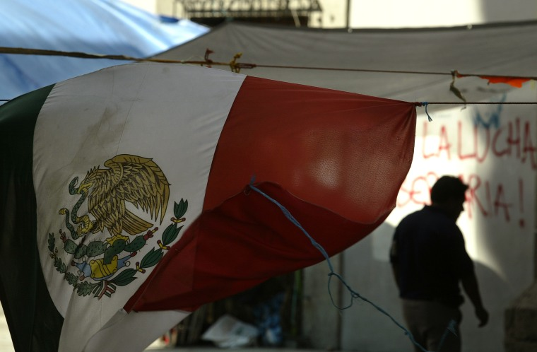 A Mexican flag flies as a Oaxaca's Popular Assembly (APPO) member walks in downtown, Saturday, Oct. 28, 2006, in Oaxaca City, Mexico.