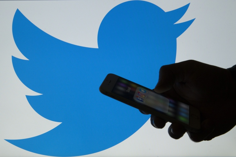 Image: A man holds a cellphone in front of a twitter logo