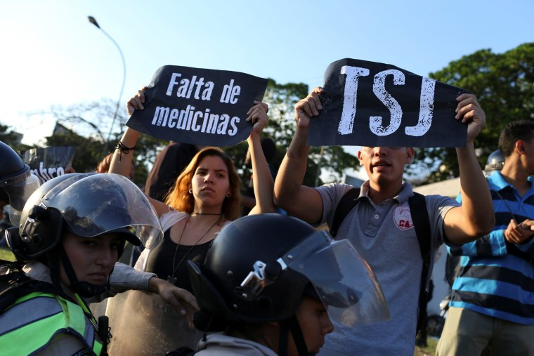 "Image: Opposition supporters holding placard that reads, ""Shortage of medicines"" and ""TSJ"", shout slogans in front of the riot police during a protest in Caracas"