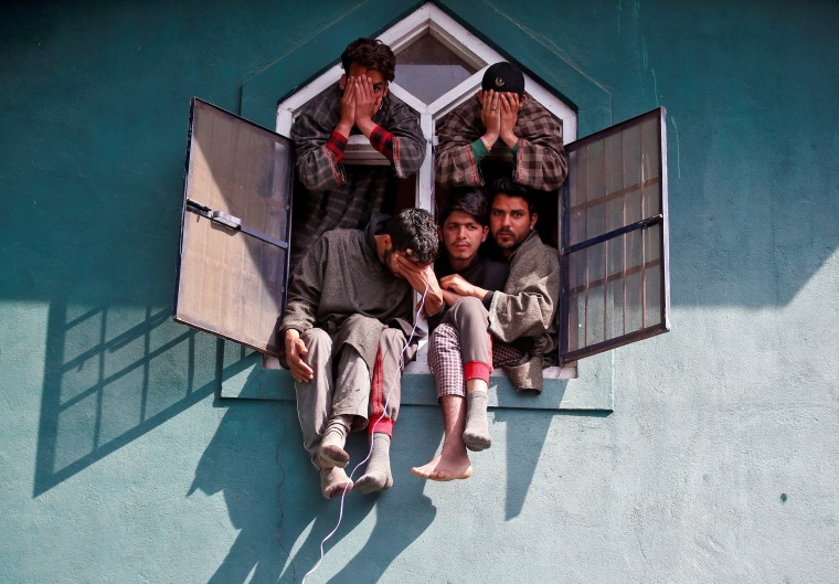 Image: People react as they sit in a window of a mosque during the funeral of Tauseef Ahmad Wagay, a suspected militant, who was killed in a gun battle with Indian army in Chadoora, in Yaripora