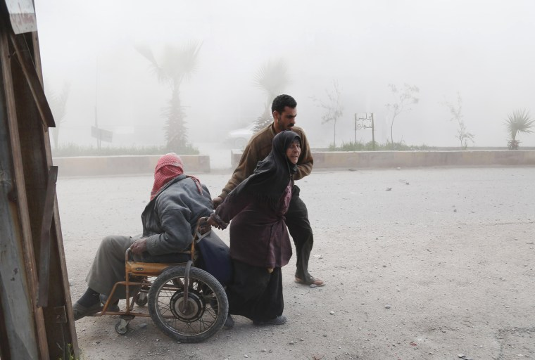 Image: A Syrian woman pulls her husband on a wheelchair as they evacuate from their home following a reported air strike on the rebel-controlled town of Hammuriyeh