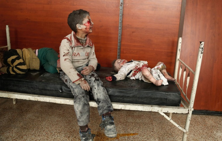 Image: Wounded Syrian children cry as they wait to receive treatment following a reported air strike on the rebel-controlled town of Hammuriyeh, in the eastern Ghouta regio