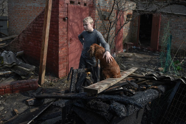 Image: A local boy with his dog stands near his destroyed home after an explosion and a fire at the ammunition depot of the Ukrainian Armed Forces in the the city of Balakiya, Kharkiv area, Ukraine