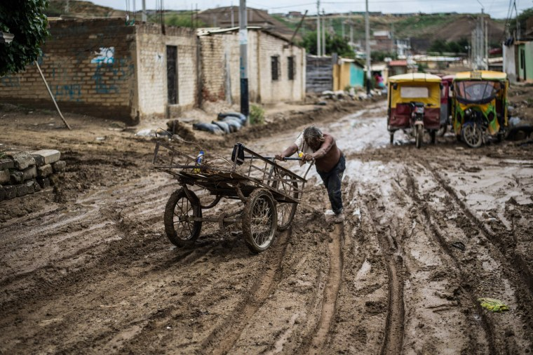 Image: A local resident pushes his cart through the mud after the flooding caused by recent rains, in the province of Paita in Piura, northern Peru, on March 24, 2017.