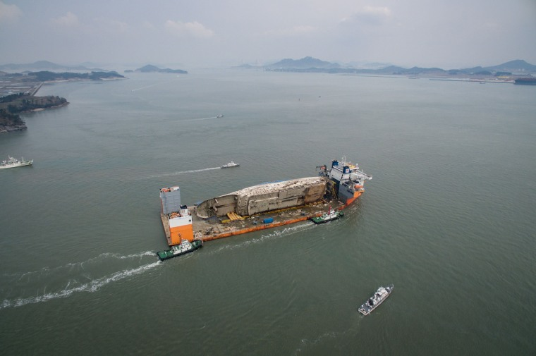 Image: This aerial general view shows the wreck of South Korea's Sewol ferry mounted on a semi-submersible barge during its arrival at a port in Mokpo on March 31, 2017.