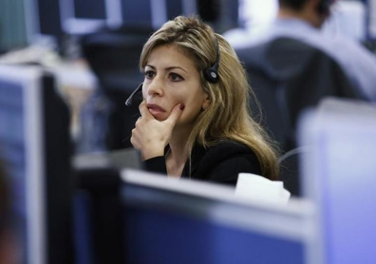 A worker on IG Index's trading floor looks at her computer screens as markets tumble globally, in London