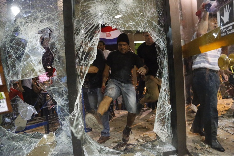 Image: A man kicks at a shattered window of the congress building during clashes between police and protesters.