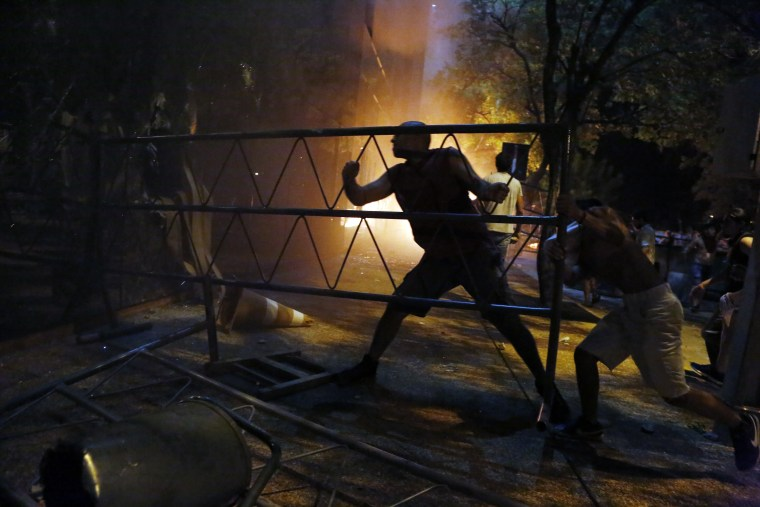 People ram a barrier into the Congress building during clashes between police and protesters in Asuncion, Paraguay, March 31, 2017.