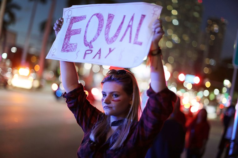 "Image: A protester holds a sign reading ""Equal Pay"" as she joins with others during A Day Without A Woman demonstration"