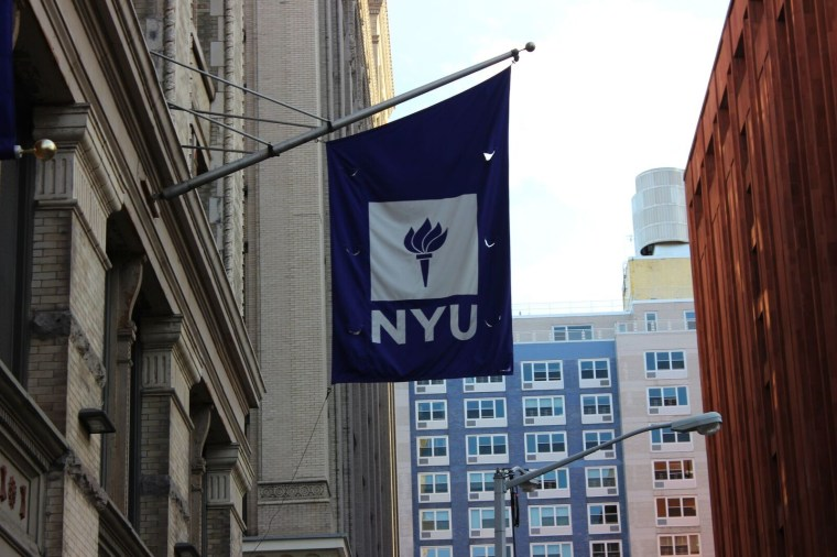 A flag of NYU outside of the buildings.