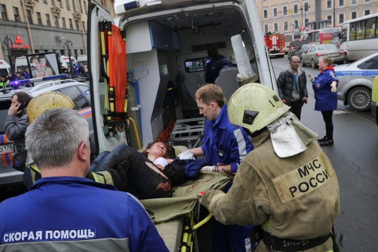 Image: An injured person is helped by emergency services outside Sennaya Ploshchad metro station following explosions in St. Petersburg