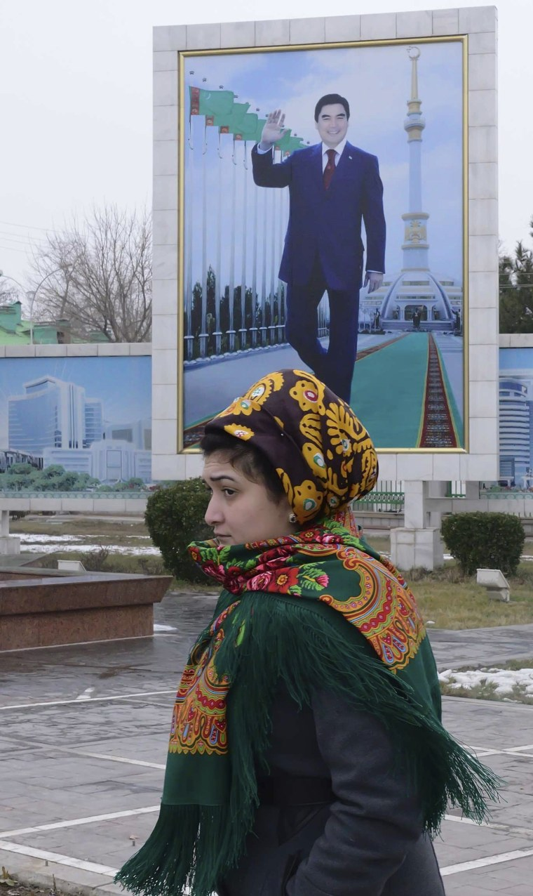 Image: A woman walks past a board displaying a portrait of Turkmenistan's President Berdimuhamedov in Ashgabat