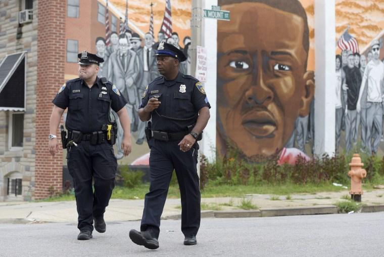 Image: Baltimore police walk near a mural depicting Freddie Gray