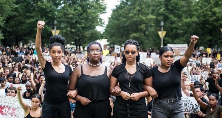 Eva Lewis (2nd from the left) led a peaceful protest of 2,000 people, in one of Chicago's busiest intersections.