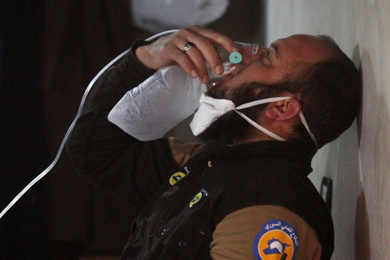 Image: A civil defense member breathes through an oxygen mask, after what rescue workers described as a suspected gas attack in the town of Khan Sheikhoun in rebel-held Idlib