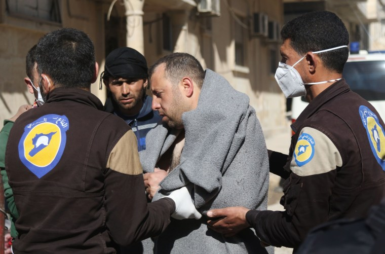 Image: A Syrian man is taken by civil defense workers to a small hospital