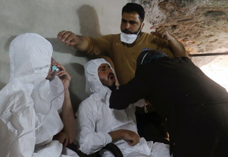 Image: A man breathes through an oxygen mask as another one receives treatments, after what rescue workers described as a suspected gas attack in the town of Khan Sheikhoun in rebel-held Idlib