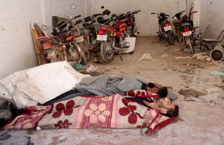 Image: Bodies lie in the parking area of a hospital in Khan Sheikhun