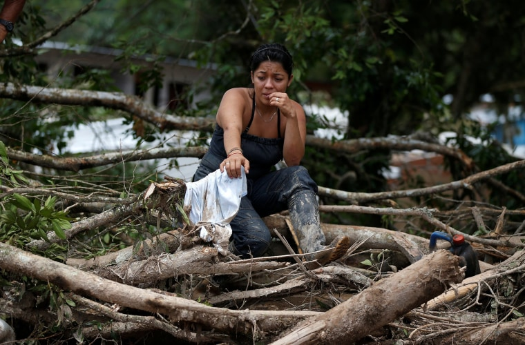 Image: A woman is seen on a destroyed street after flooding and mudslides caused by heavy rains in Mocoa