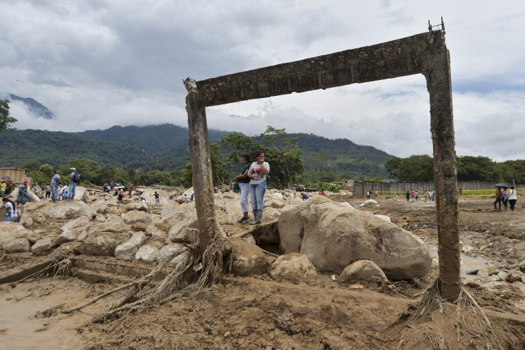 Image: Women stare at damages caused by mudslides