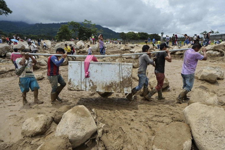 Image: People carry their belongings amidst the rubble left by mudslides
