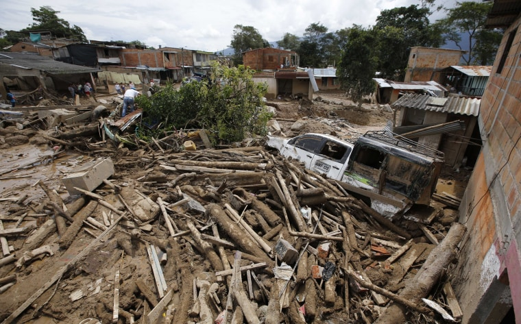 Image: Tree trunks and mud cover a street in Mocoa