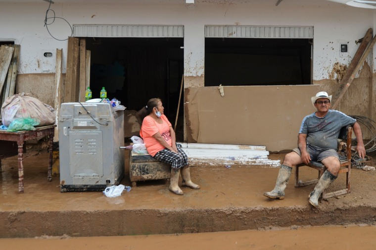 Image: A couple wait outside their home damaged by mudslides