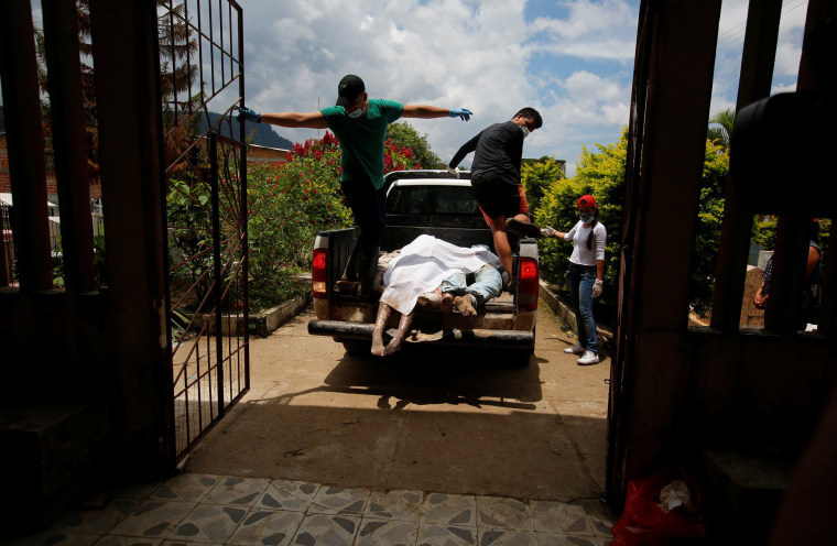 Image: Men arrive in a vehicle with bodies to be identified after flooding and mudslides caused by heavy rains in Villagarzon