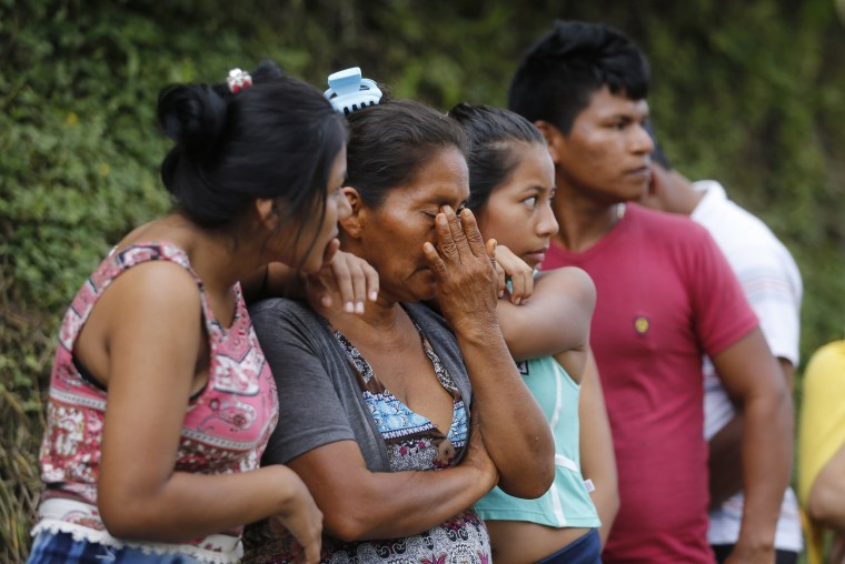 Image: People line up outside a cemetery to looking for their missing relatives in Mocoa