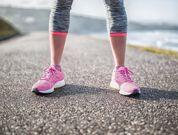 Spain, Gijon, legs of sportive young woman on path