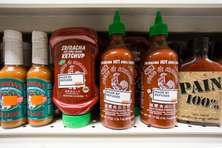 """A """"Made By Refugee"""" sticker on a bottle of Sriracha hot sauce."""