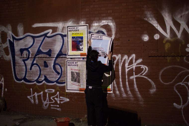 Kien Quan installing a mural in Bushwick, Brooklyn, with large Made by Refugee posters.