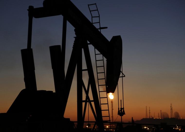 An oil pump works at sunset Monday, Jan. 18, 2016, in the desert oil fields of Sakhir, Bahrain.
