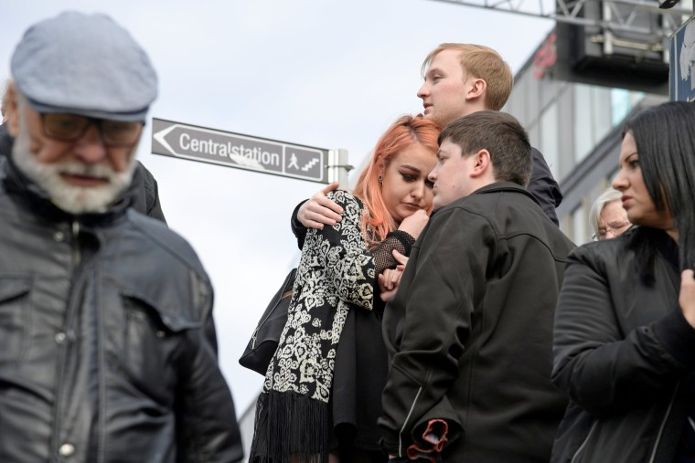 Image: A young woman, an evacuee from the central train station, reacts after three people were killed when a truck crashed into a department store, Ahlens, in central Stockholm