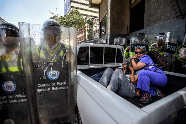 Image: People protect themselves during clashes in Caracas