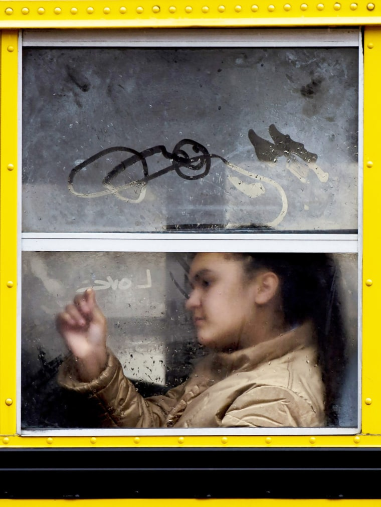 Image: A girl draws with the condensation on a school bus window