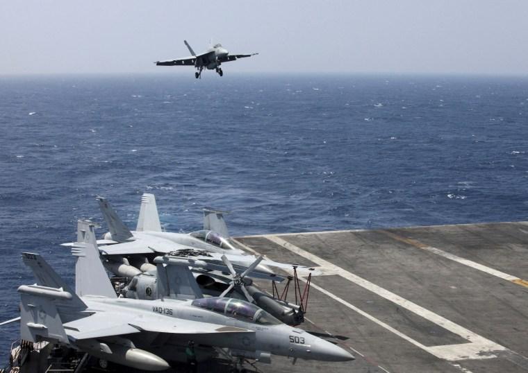 Image: A U.S. Navy F18 fighter jet lands on the U.S. Navy aircraft carrier USS Carl Vinson