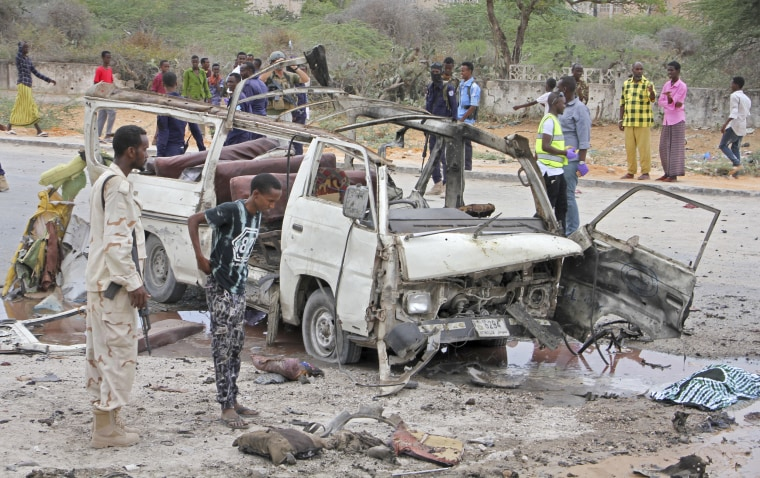 Image: A Somali soldier stands by the wreckage of a minibus