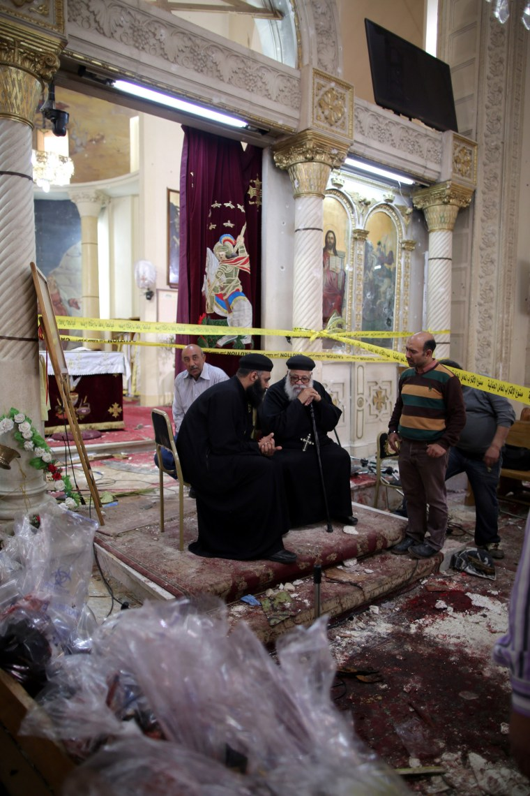 Image: Coptic priests sit among the damages next to security personnel investigating the scene in Tanta.
