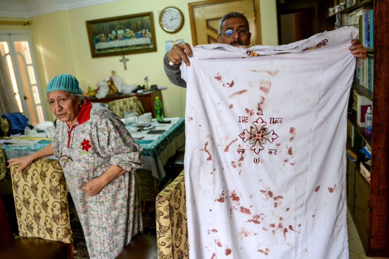 Image: A man holds a Coptic clergy cloth with blood stains on it at the Mar Girgis church after the explosion, which took place about 90km north of Cairo.