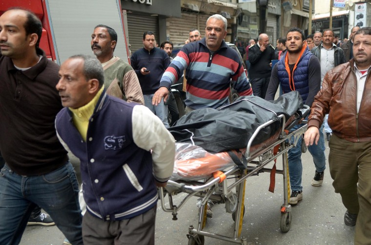 Image: Rescue workers push a stretcher with a victim outside the Saint Mark's Coptic Cathedral in Alexandria.