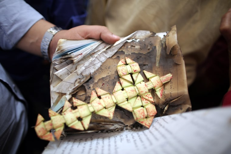 Image: A palm leaf is stained with blood inside the Mar Girgis church.
