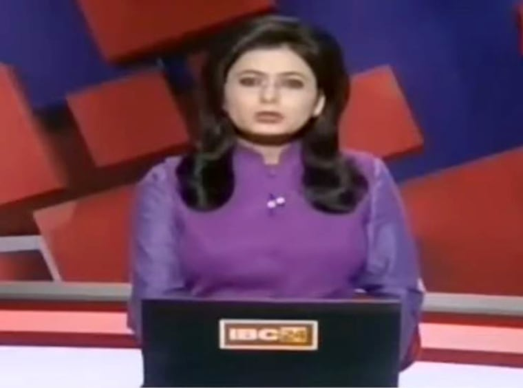Image: Indian television news anchor Supreet Kaur reads the morning news broadcast, where she learned about her husband's death while giving the report.