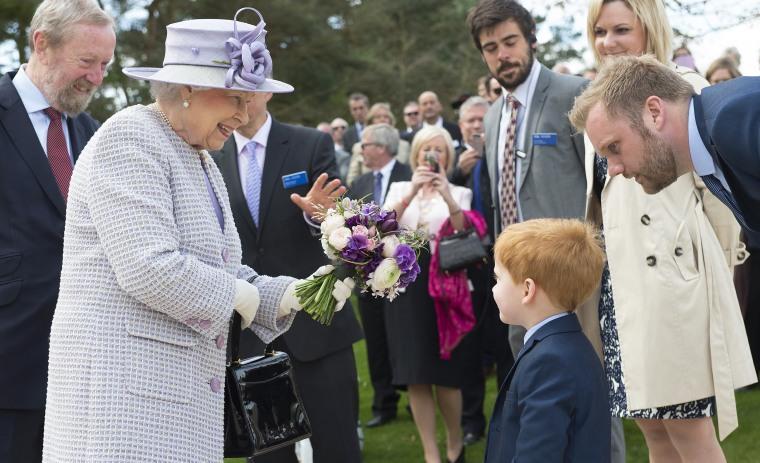 Queen Elizabeth II accepts a bouquet of flowers