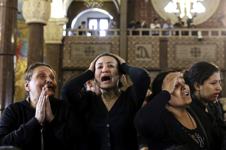 """Image: Women cry during the funeral for those killed in the Palm Sunday attack in Alexandria, at the Mar Amina church. Women wailed as caskets marked with the word \""""martyr\"""" were brought into the Mar Amina church in the coastal city of Alexandria."""