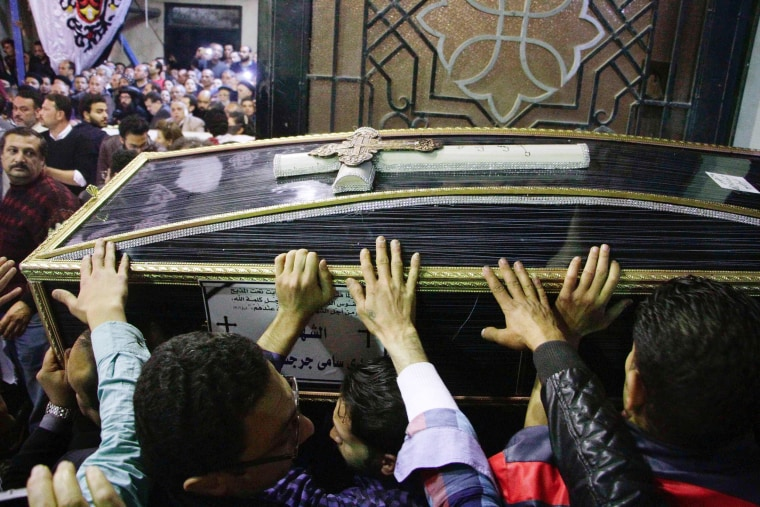 Image: Egyptian Christians carry a coffin during the late night funeral of the victims from the Mar Girgis Coptic Orthodox Church in Tanta, April 9.