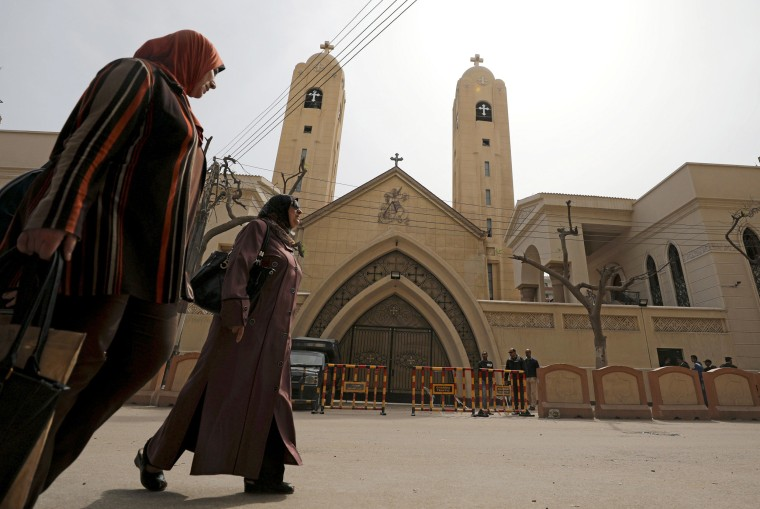 Image: Women walk by the church in Tanta, April 10.